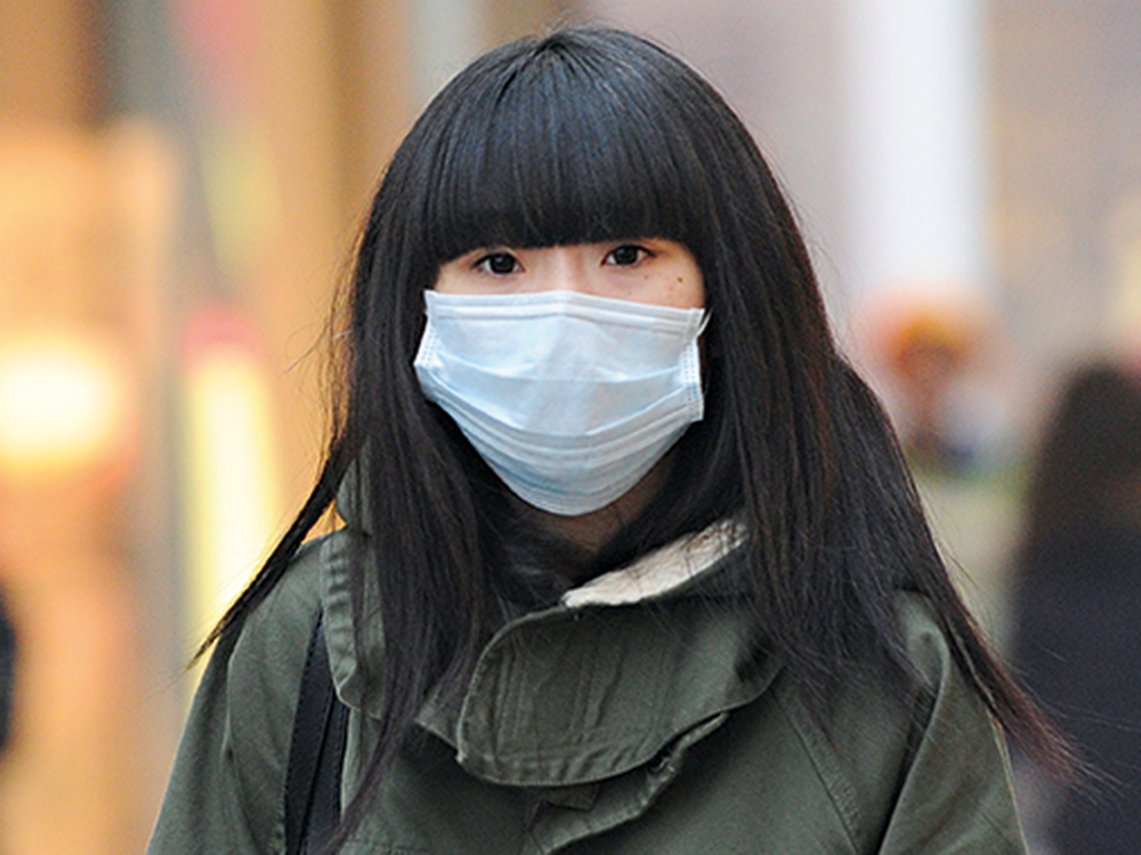 A woman wears a mask as she makes her way along a street in Beijing