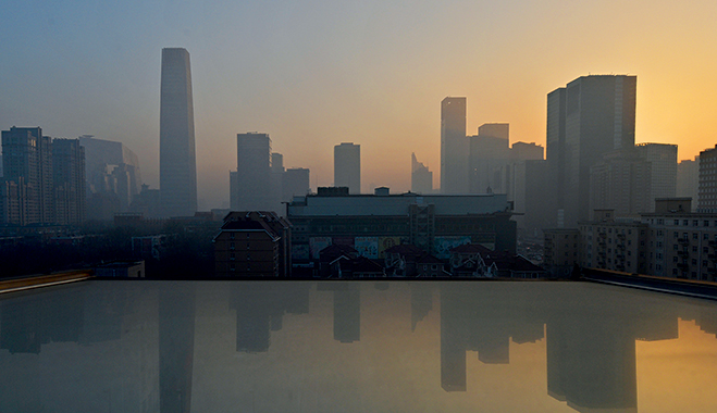 Smog hangs over the skyline as the sun rises over the central business district in Beijing
