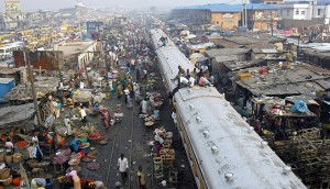 Commuters sit on top of a train at a rail track in the Oshodi district of Lagos. While Nigeria's population rapidly expands, housing has run short - presenting an opportunity for investors