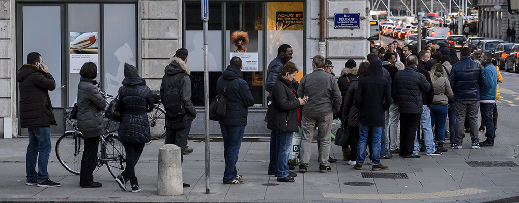 People queue outside a currency exchange office in Geneva, waiting to change their Swiss francs. The Swiss government's decision to peg its currency to the euro has severely damaged the forex industry