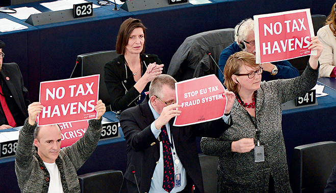 European Parliament members hold placards during a voting session on a censure motion on the European Commission