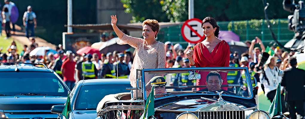 President Dilma Rousseff waves as she heads to the National Congress in Brasília to take the oath of office for her second term next to her daughter Paula