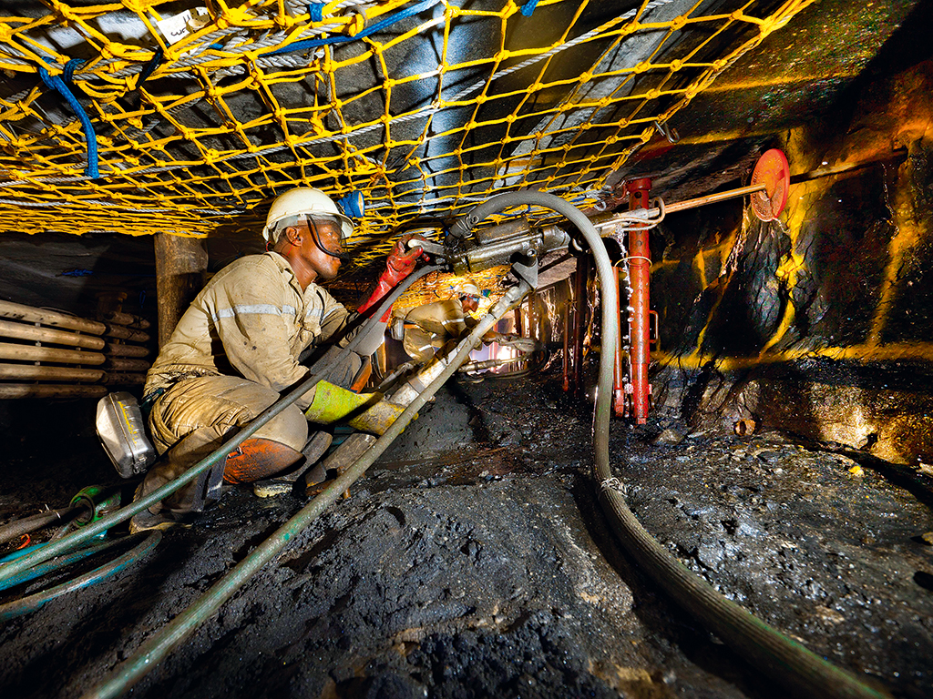 A miner drilling under strike nets in the Khomanani Mine, near Rustenburg, South Africa