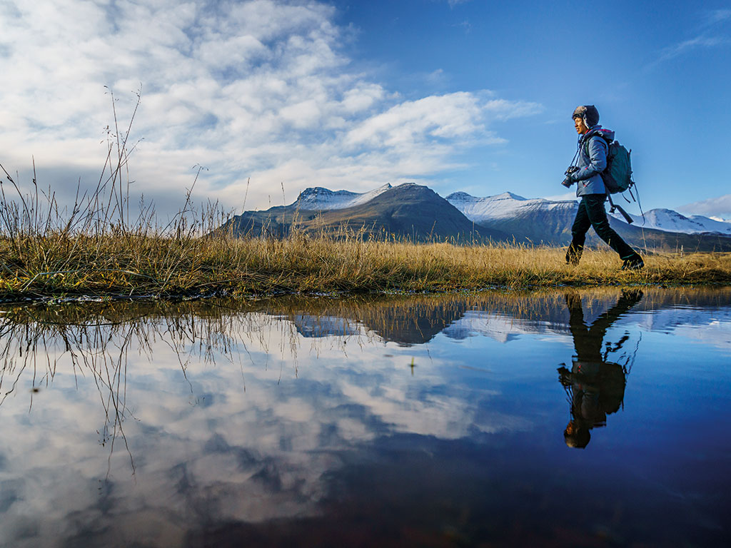 A woman hiking beside one of Iceland's iconic lakes. Hiking, sailing and other activities have seen tourism grow by 100 percent in the country since 2006