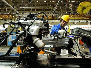 An employee works in a car manufacturing plant in Qingdao, China. China's automobile industry was one of few to show signs of growth in July
