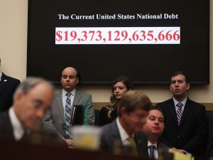 A clock showing the current national debt of the US is seen during a hearing before the House Financial Services Committee. The IMF has warned governments over increasing global debt levels