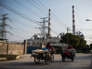 Chinese workers take their carts past a power plant in Shanghai. The US has launched a complaint against China, claiming Chinese trade management of rice, wheat and corn is creating an uneven playing field for US exporters