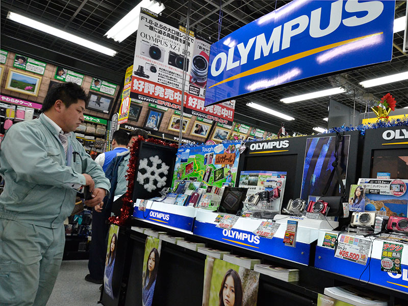 Olympus cameras on sale in Tokyo, Japan. Six former Olympus executives have been collectively charged with $520m worth of damages related to a scandal that came to light in 2011
