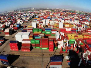 Containers are offloaded at Qingdao Port in China. There are concerns that the country would benefit from artificially cheap exports were it to gain market economy status