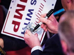 Donald Trump signs a $100 bill during the election campaign