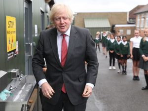 Britain's Prime Minister Boris Johnson gestures after washing his hands at a sink in the playground during a visit to Bovingdon Primary School