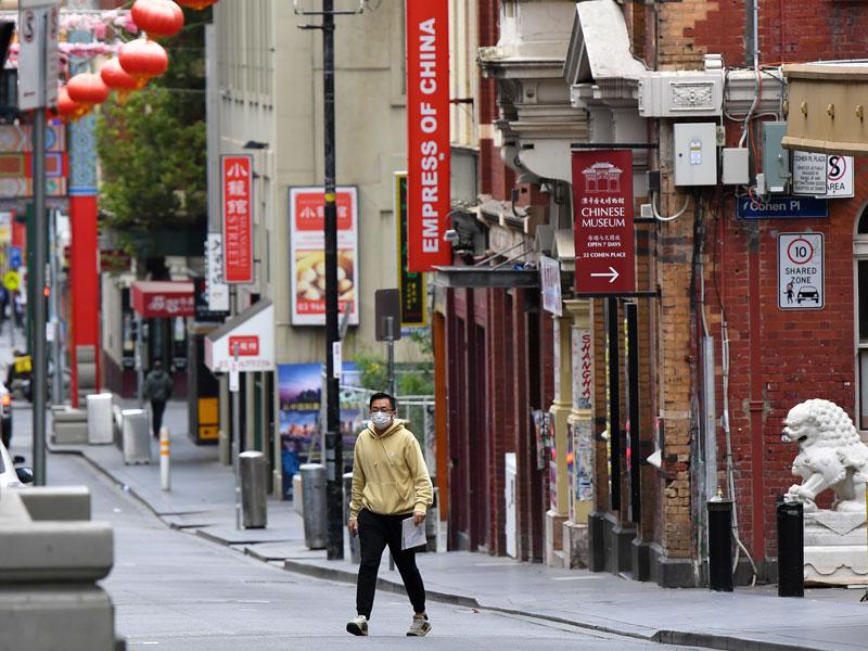 Мужчина в маске переходит дорогу в Чайнатауне в Мельбурне, Австралия.